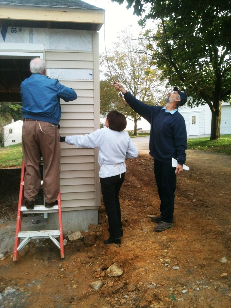 Dale and Anna Mae work on siding while Jim takes measurements.